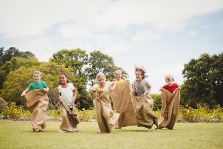Photo pour Children having a sack race in park on a sunny day - image libre de droit