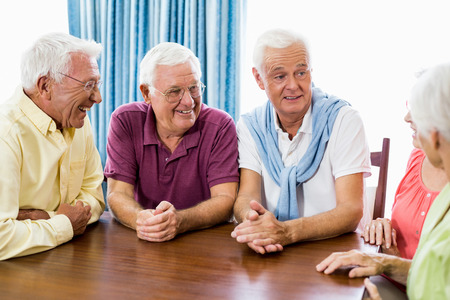 Seniors talking at table in a retirement home