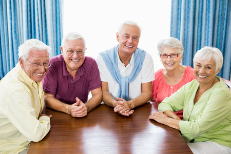 Smiling seniors sitting at table in a retirement home