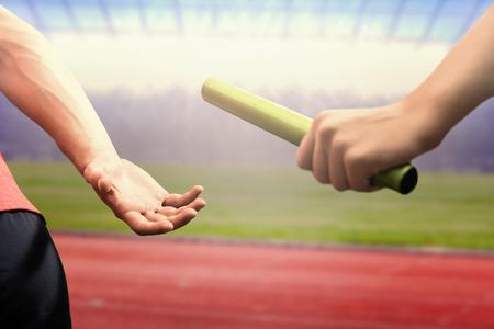 Photo pour Athlete passing a baton to the partner against race track - image libre de droit