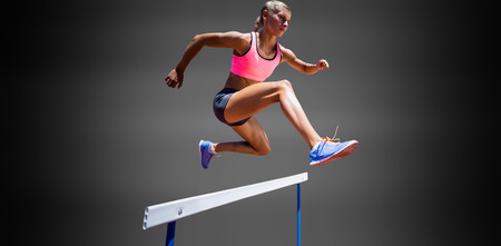 Sporty woman jumping a hurdle against black background