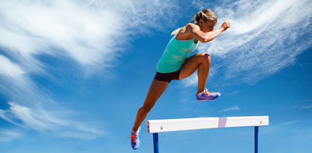 Athlete woman jumping a hurdle against view of a blue sky