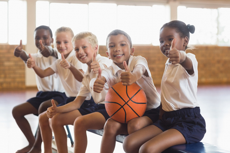 Photo pour Smiling students with basketball showing thumbs up in school gym - image libre de droit