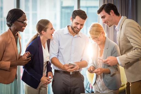 Photo pour Group of business people interacting using mobile phone in the office - image libre de droit