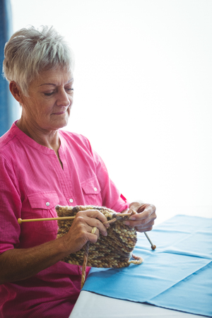 Retired concentrate woman doing some knitting