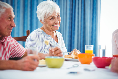 Senior smiling woman during breakfast in a retirement home