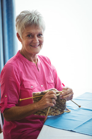 Portrait of a retired smiling woman doing some knitting
