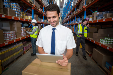 Business worker looking at digital tablet in warehouse