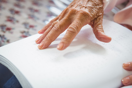 Senior woman using braille to read in a retirement home