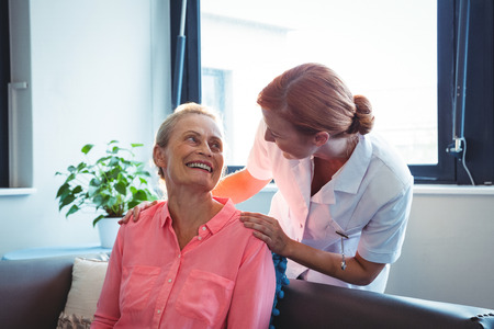Nurse and senior woman looking at each other in a retirement home