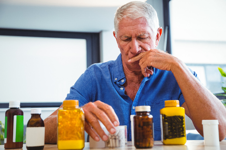 Senior man holding medicine in a retirement home