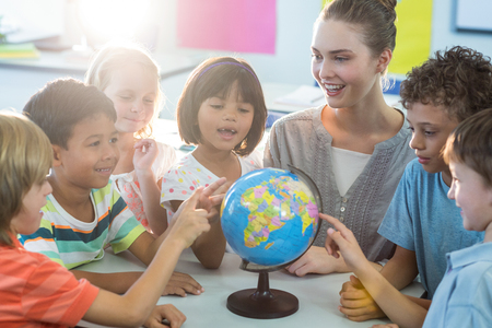 Photo for Smiling female teacher showing globe to schoolchildren in classroom - Royalty Free Image