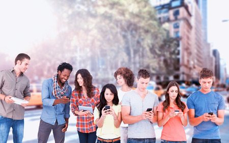Four people standing beside each other and texting on their phones against new york street