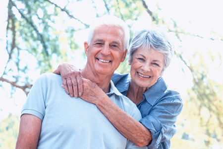 Happy old couple smiling in a park on a sunny day
