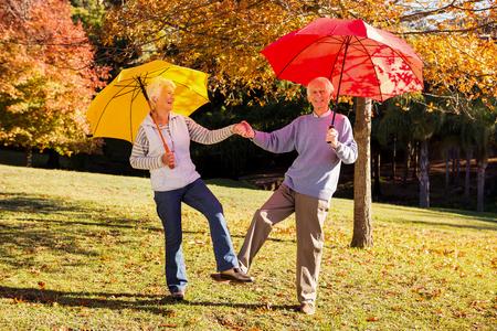 Senior couple dancing with umbrellas in a park