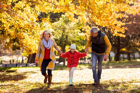 Joyful family walking against trees at park during autumn