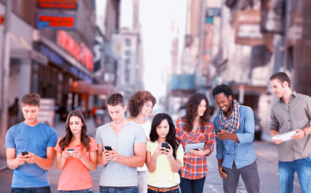 Four people standing beside each other and texting on their phones against picture of a city