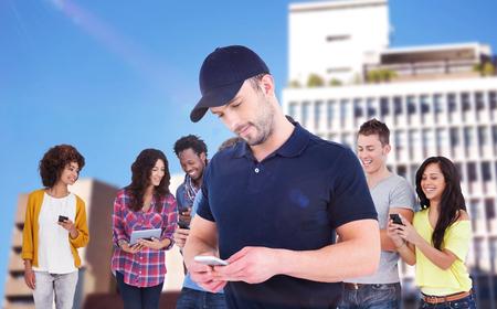 Smiling man using mobile phone  against defocused image of buildings