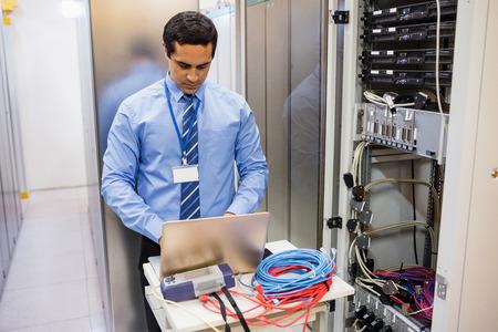Focused technician working on laptop in server room
