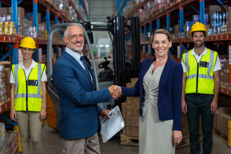 Portrait of warehouse manager shaking hands with client in warehouse