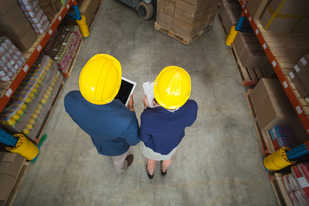 Rear view of warehouse manager and client standing in warehouse