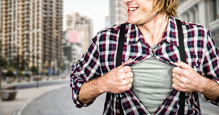 Funny blond hipster taking off his shirt against new york street