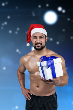 Muscular man in santa hat against starry dark blue night sky