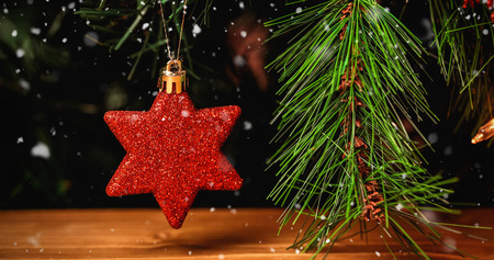 Snow falling against close-up of red star hanging on christmas tree