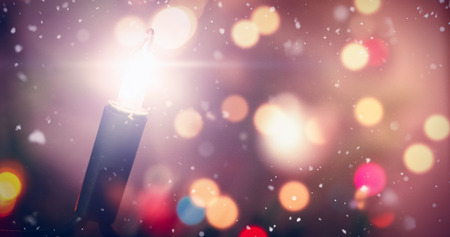Snow falling against close-up of fairy light