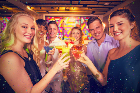 Group of friends toasting glass of cocktail in bar against flying colours