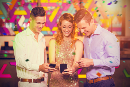 Smiling friend looking at mobile phone against flying colours