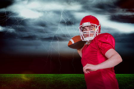 3D American football player throwing a ball against stormy dark sky with lightning bolts