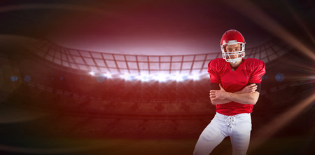 3D Portrait of serious american football player with arms crossed against red background with vignette