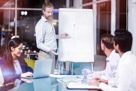 Businessman discussing graph on white board with colleagues in office