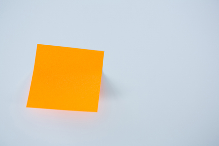 Close-up of orange adhesive note against a white background