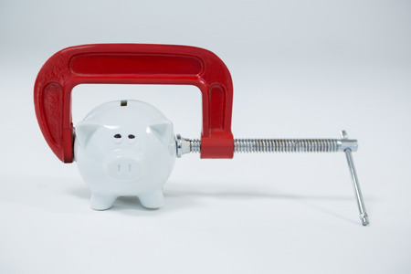 Clamp cutting piggy bank on white background