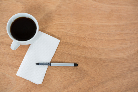 Close-up of black coffee with tissue paper and pen on wooden table