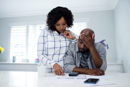 Worried couple interacting while checking the bills at home