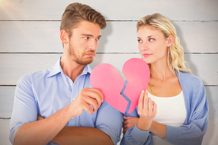 Couple holding two halves of broken heart against painted blue wooden planks