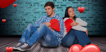 Young couple sitting on floor with broken heart against hardwood floor against turquoise  wall