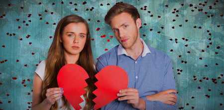 Couple holding broken heart against blue paint splashed surface