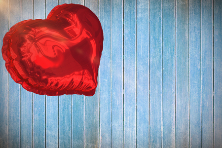 Red heart balloon against wooden planks 3d