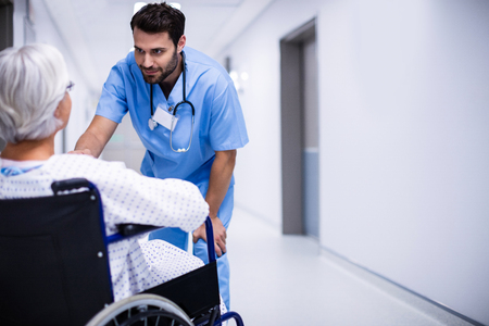 Male doctor interacting with senior patient on wheelchair in the corridor