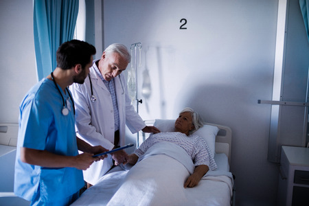 Doctors comforting senior patient on bed in hospital