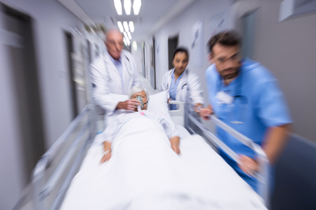 Doctor and nurse pushing emergency stretcher bed in corridor at hospital