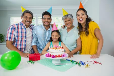 Portrait of happy multigeneration family celebrating birthday party at home