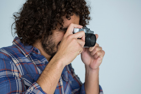 Male photographer with old fashioned camera in studio