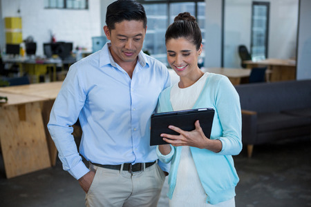Smiling business colleagues discussing over digital tablet in office