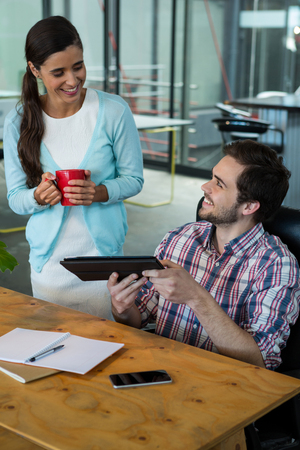 Smiling business executives discussing over digital tablet in office