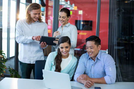 Businesspeople using laptop and digital tablet in office